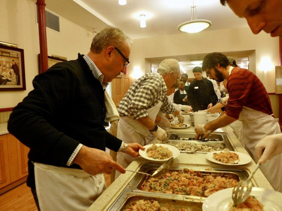 Workers get paella ready for a Ministry of Caring Spanish dinner
