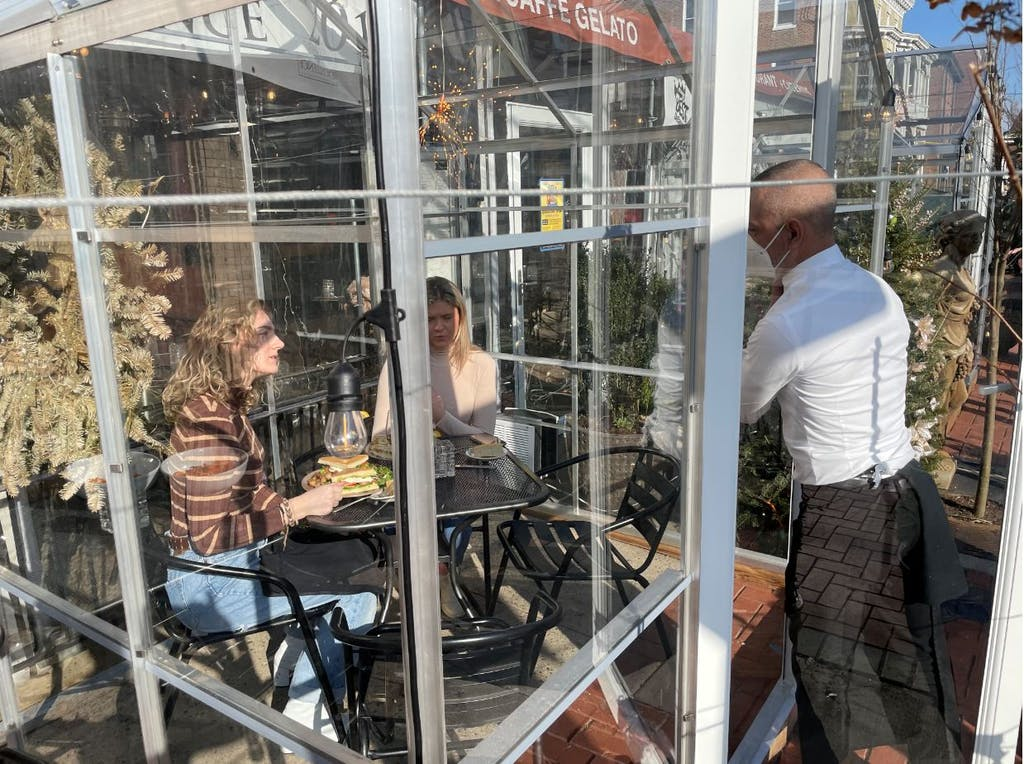 Caffe Gelato customers enjoy sun in one of its solo greenhouses