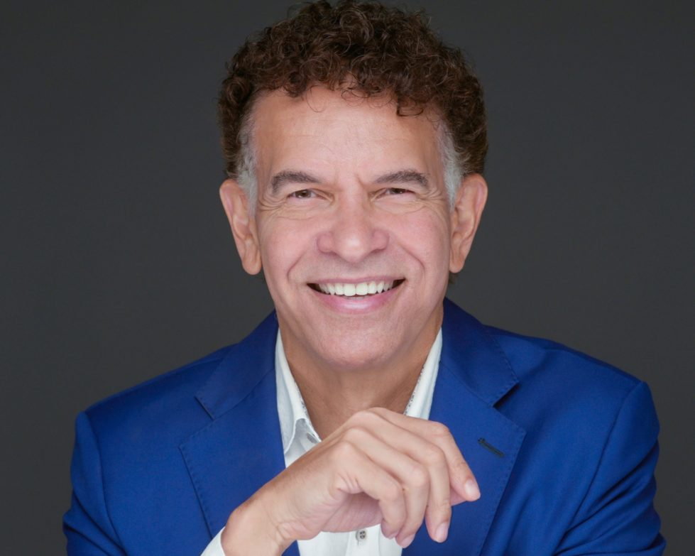 Brian Stokes Mitchell wearing a blue shirt and smiling at the camera