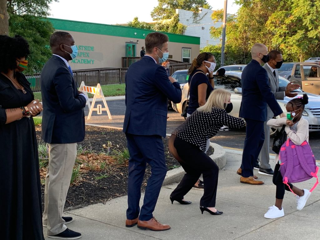 a group of people standing on a sidewalk